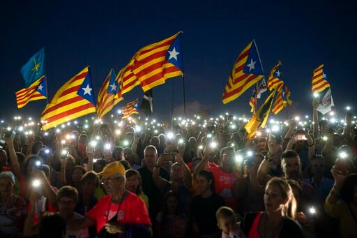 "(AP Photo/Felipe Dana, File). FILE - In this Sunday, Sept. 30, 2018 file photo, pro-independence demonstrators wave ""esteladas"" or independence flags, as they sing in a field overlooking the Lledoners prison in Sant Joan de Vilatorrada, about 50 kilome..."