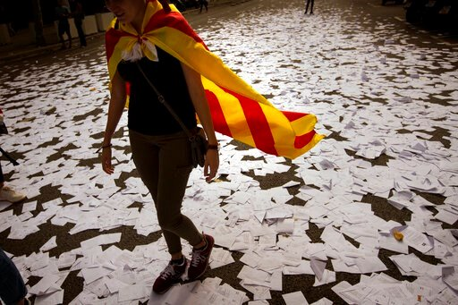 (AP Photo/Emilio Morenatti, File). FILE - In this Tuesday Oct. 3, 2017 file photo, a woman wearing an Estelada or independence flag, walks along a street covered with referendum ballots thown by pro-independence demonstrators, during a rally in Barcelo...