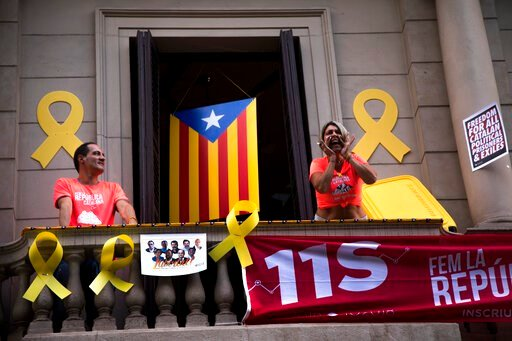(AP Photo/Emilio Morenatti, File). FILE - In this Tuesday, Sept. 11, 2018 file photo, a woman shouts slogans from her balcony during the Catalan National Day in Barcelona, Spain. Spain's Supreme Court is bracing to hold the nation's most sensitive tria...